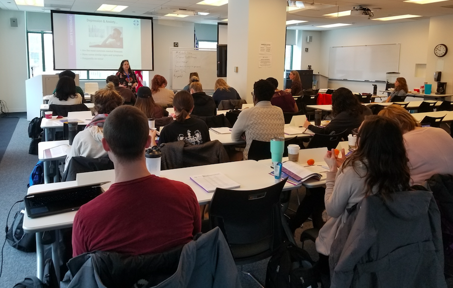 large classroom of individuals listening to a presentation