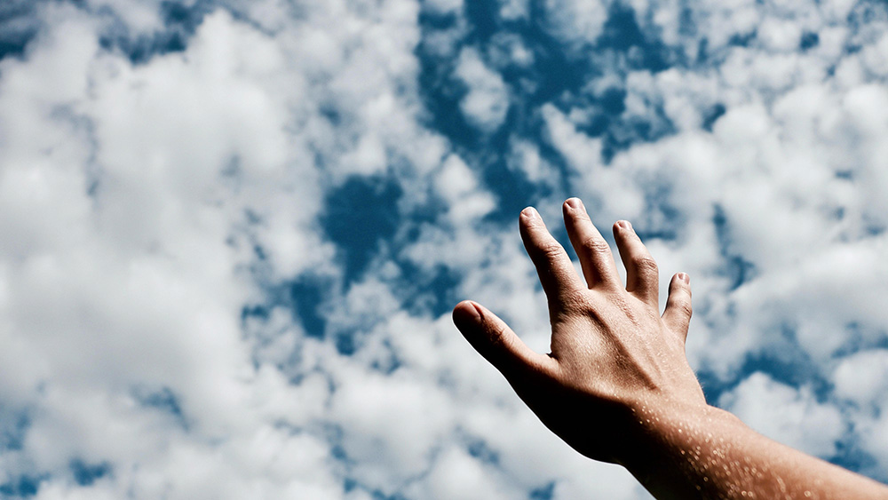 handing reaching toward blue sky with clouds