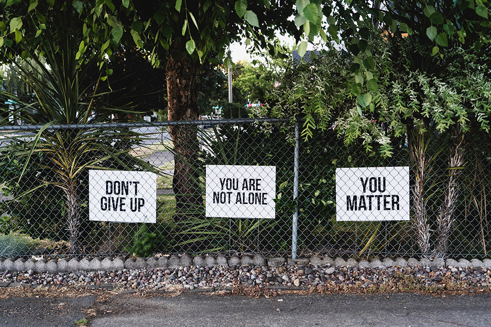 don't give up, you are not alone, you matter posters on a fence